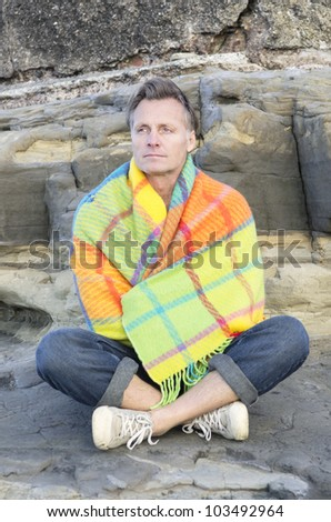 A portrait of a mature man in his forties sitting on a rock wrapped in a colorful blanket. - stock photo