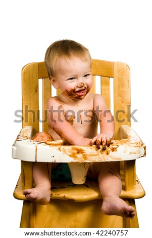 A portrait of a messy baby boy isolated eating chocolate. - stock photo