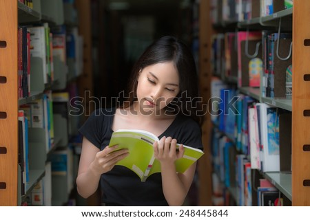A portrait of a mixed race college asia student at campus in library and read a book - stock photo