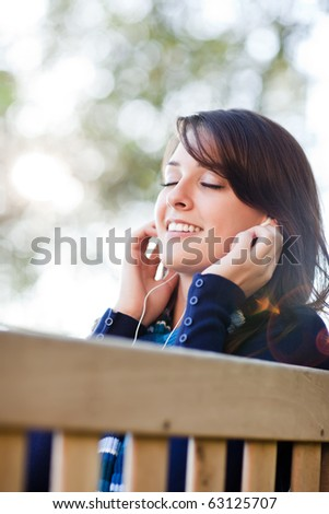 A portrait of a mixed race college student listening to music at campus - stock photo