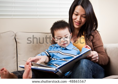 A portrait of a mother and a son reading a book