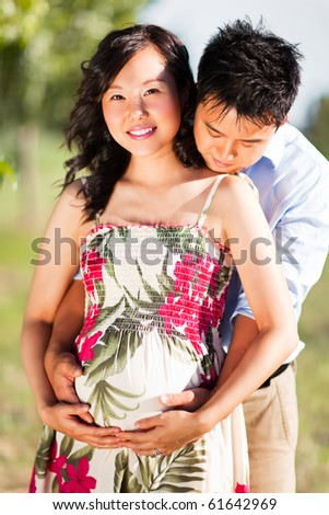 A portrait of a pregnant wife with her husband - stock photo