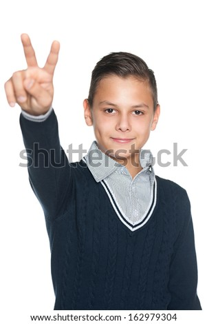 A portrait of a preteen boy shows victory sign on the white background - stock photo