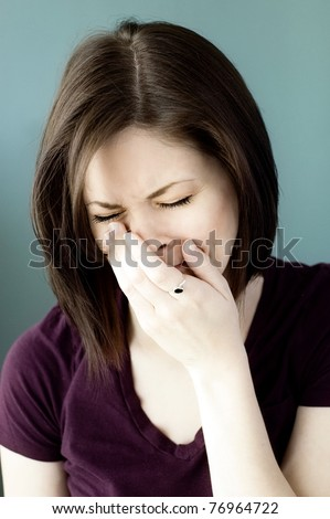 A portrait of a sad young woman crying with her eyes closed.