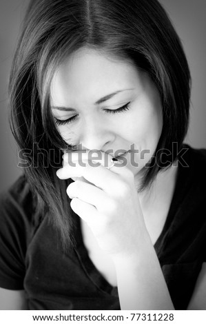 A portrait of a sad young woman crying with her eyes closed in black and white.