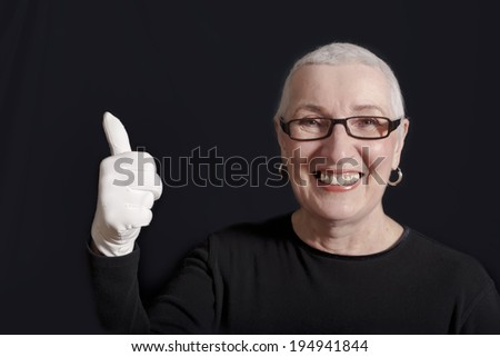 A portrait of a senior woman with short white hair, dark glasses and a white gloved hand with the thumbs up gesture. - stock photo