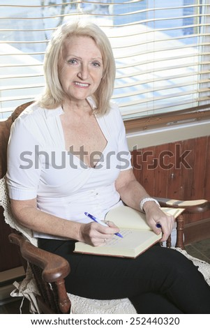 A Portrait of a Senior woman Write on Book