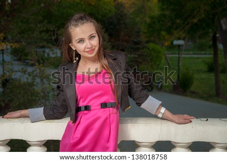 A portrait of a smiling beautiful woman outdoors pink dress in the evening - stock photo