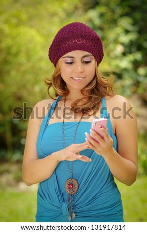 A portrait of a smiling beautiful woman texting with her phone - stock photo