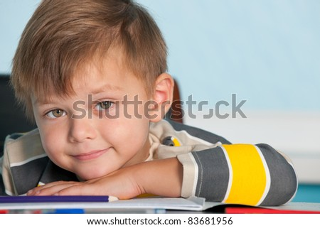 A portrait of a smiling boy at the desk - stock photo