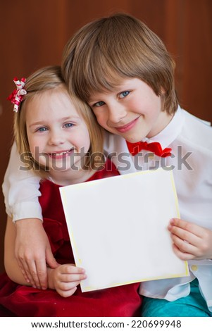 A portrait of a smiling cute little boy and girl embracing each other with empty blank in hands, isolated on brown, close up. Holidays concept. Invitation. Funny kids. Happy family. - stock photo