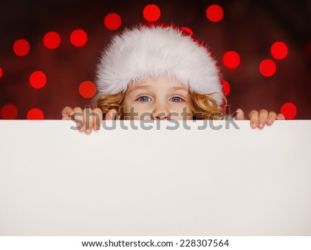 A portrait of a smiling cute little girl in Santa hat looking out from behind empty blank with her hands on it, isolated against Christmas glitter close up. Holidays concept. Invitation. Funny kids.  - stock photo