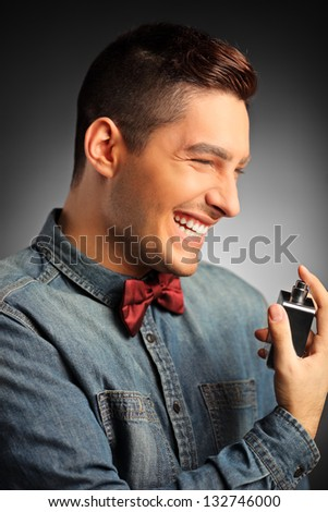 A portrait of a smiling handsome male applying perfume - stock photo