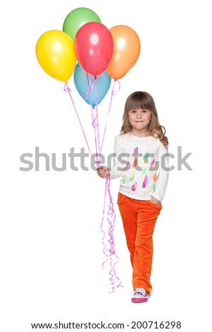 A portrait of a smiling little girl with balloons against the white background - stock photo