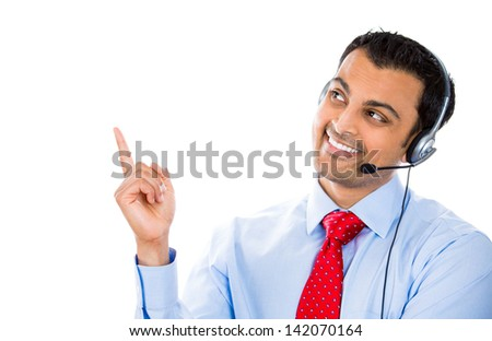 A portrait of a smiling male customer representative pointing at a copy space while talking on a hands free device - stock photo