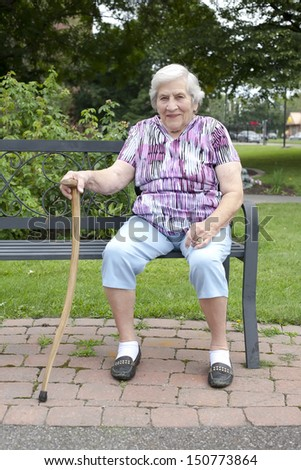 A portrait of a smiling senior female sitting on a park bench outside on a warm summer day. - stock photo