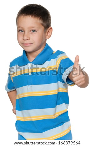 A portrait of a smiling young boy holding his thumb up on the white background - stock photo