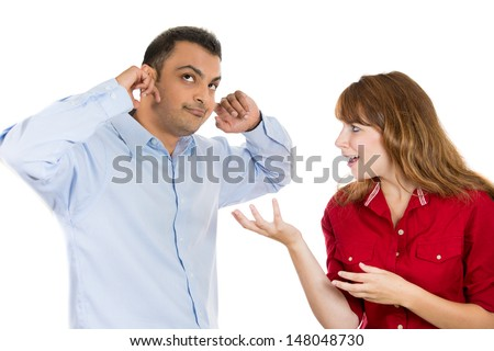 A portrait of a stressed couple going through hard times in their relationship, isolated on a white background . Young woman trying to explain something to a man, he is annoyed and closes his ears. - stock photo