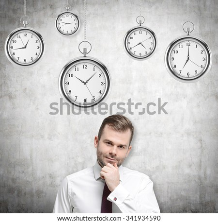 A portrait of a thinking handsome businessman who is holding his own chin. Several models of pocket watches are hovering in the air. A concept of a value of time in business. Concrete background. - stock photo