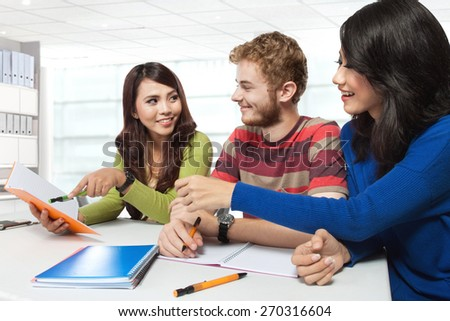 A portrait of a three multicultural student, studying together - stock photo