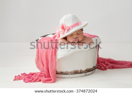A portrait of a three week old, sleeping, newborn, baby girl wearing a fancy, brimmed Easter hat with pink flowers. She is sleeping in a vintage, white, wooden bucket. - stock photo