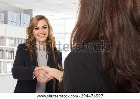 A portrait of a two young businesswoman making a deal and shaking hands in the office