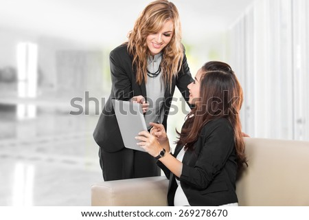 A portrait of a two young businesswoman with a tablet