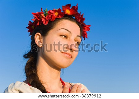 A portrait of a Ukrainian girl in a traditional outfit and a wreath of live flowers