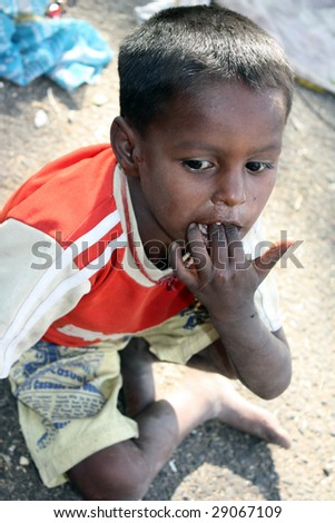 A portrait of a unhygenic poor kid from India, sucking on his dirty fingers.