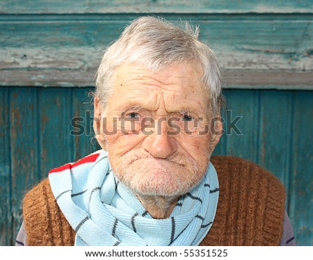 A portrait of a very old man, 96 years old near his house. - stock photo