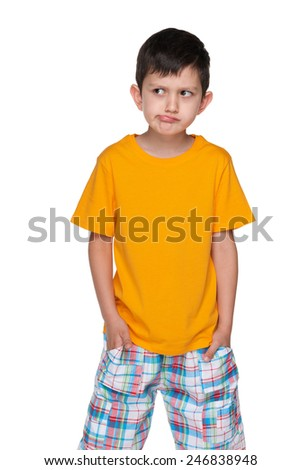 A portrait of a very thoughtful little boy in a yellow shirt on the white background
