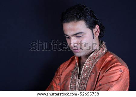 A portrait of a worried Indian man, in a traditional attire. - stock photo