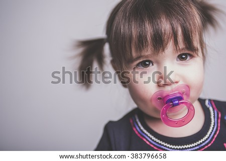 A Portrait of a 2 year old girl on studio suck - stock photo
