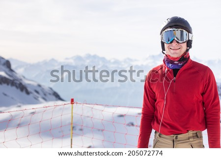 A portrait of a young adult in front of snow mountains ready to ski! - stock photo