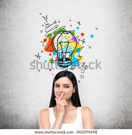 A portrait of a young artful brunette lady who is trying to create a new idea for some business project or case study. A colourful lightbulb as a concept of a new idea is drawn on the concrete wall. - stock photo