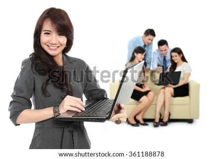 A portrait of a young asian businesswoman, with her team behind holding laptop. isolated in white background - stock photo
