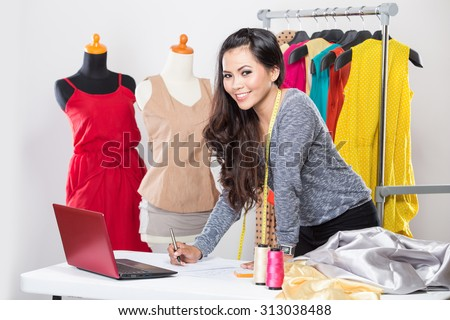 A portrait of a young asian designer woman using a laptop and smiling,clothes hanged as background - stock photo