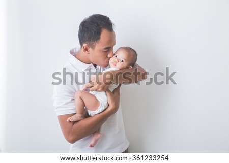 A portrait of a Young Asian father holding and kissing his adorable baby on white background - stock photo