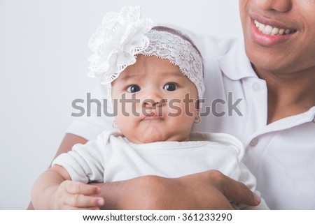 A portrait of a Young Asian father holding his adorable baby, focused on daughter's face - stock photo