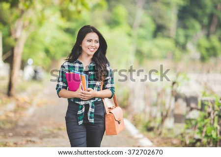 A portrait of a young asian female student holding books while  walking on the park - stock photo