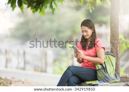 A portrait of a young Asian student sitting outdoor, holding a cellphone