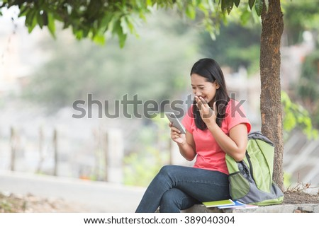 A portrait of a young Asian student sitting outdoor,reading something on the cellphone and surprised