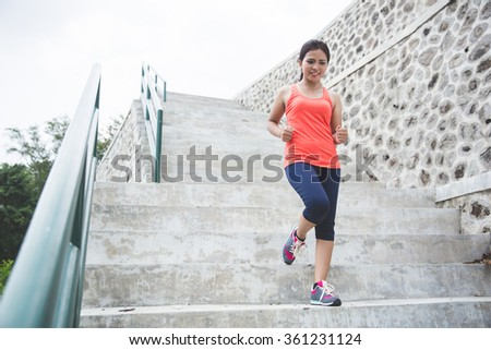 A portrait of a young asian woman doing exercise outdoor in a park, jogging up and down the stair - stock photo
