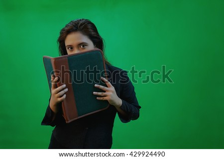 A portrait of a young asian woman smiling and gestures while standing - green screen for compositing - stock photo