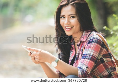 A portrait of a young asian woman using a cellphone while sitting on the park - stock photo