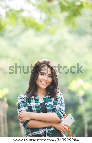A portrait of a young asian woman walking on the park