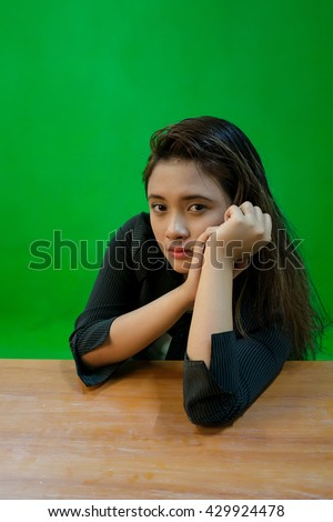 A portrait of a young asian woman with sad expression while sitting - green screen for compositing