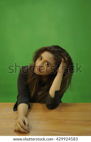 A portrait of a young asian woman with tired expression while sitting - green screen for compositing