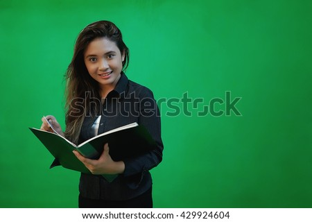 A portrait of a young asian woman writing a letter while standing - green screen for compositing - stock photo
