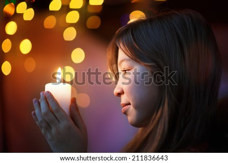 A portrait of a young beautiful girl holding a candle and looking at it with twinkling fairy lights as a background. Kids and Christmas.
